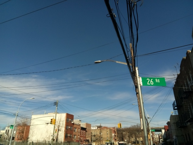telephone pole and wires crisscross in front of a blue sky. green street sign saying 26th road