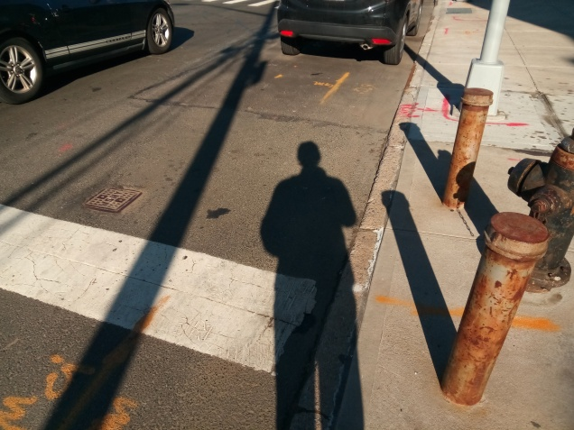spikes and lines of shadow against a shot of a nyc asphalt street, facing north. cars travelling away from the POV, suggesting motion