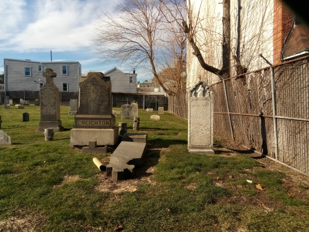 gravestones in a small yard next to a building with two story homes in the background. a gnarly tree stretches across the middle of the frame