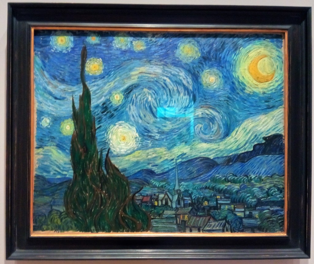 van gogh's starry night. blurry swirls of light and cloud like fuzzy eyes in a wheat sky. tall brush in the foreground. sleepy cottage houses from above, then rolling hills